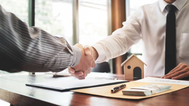 Real estate agent shaking hands with customer with house model and contract paper. stock photo