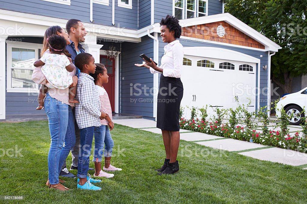 Real estate agent showing a family a house stock photo