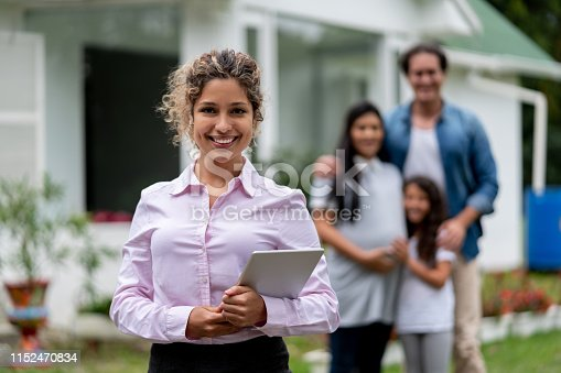 Portrait of a real estate agent showing a family a suburb house and looking at the camera smiling