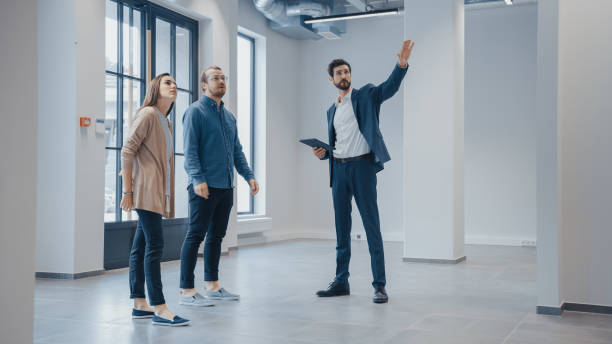 Real Estate Agent Showing a New Empty Office Space to Young Male and Female Hipsters. Entrepreneurs Meet the Broker with a Tablet and Discuss the Facility They Wish to Purchase or Rent. stock photo