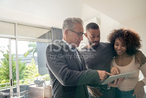 Real estate agent showing a property to a happy African American couple using a tablet computer – lifestyle concepts