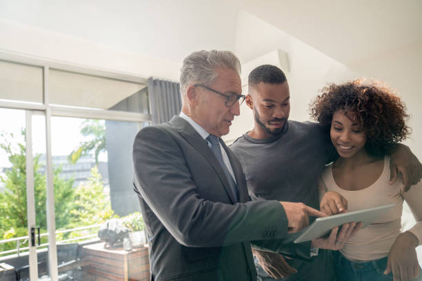 real estate agent showing a property to an african american couple - home show stock photos and pictures