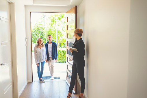 istock Real estate agent showing a young couple a new house. 1155844286