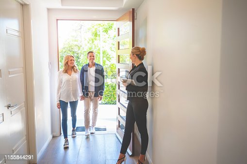 1040654052 istock photo Real estate agent showing a young couple a new house. 1155844291