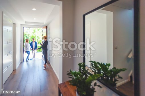 Real estate agent showing a young couple a new house. The house is contemporary. All are happy and smiling. The couple are casually dressed and the agent is in a suit. The couple are being greeted at the front door by the real estate agent. Copy space