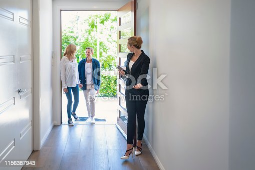 istock Real estate agent showing a young couple a new house. 1156387943