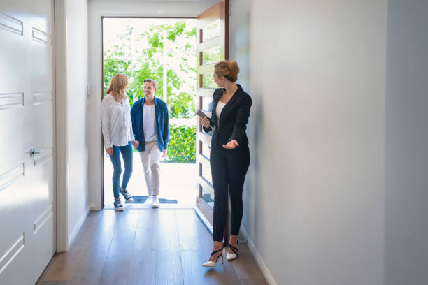 Real estate agent showing a young couple a new house. Real estate agent showing a young couple a new house. The house is contemporary. All are happy and smiling. The couple are casually dressed and the agent is in a suit. The couple are being greeted at the front door by the real estate agent. Copy space model home stock pictures, royalty-free photos & images
