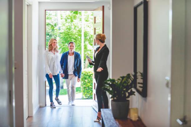 Immobilienmakler zeigt einem jungen Paar ein neues Haus. – Foto
