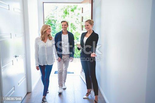 1040654052 istock photo Real estate agent showing a young couple a new house. 1156387946