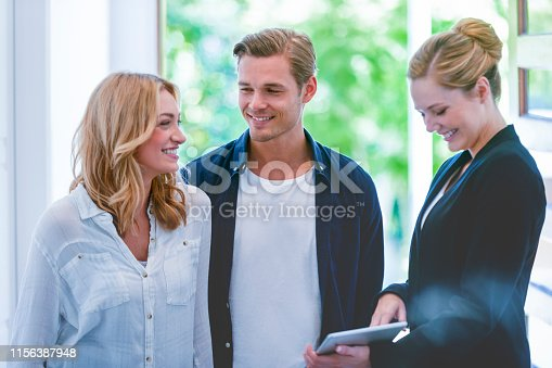 1040654052 istock photo Real estate agent showing a young couple a new house 1156387948