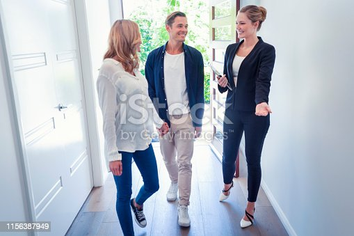 1040654052 istock photo Real estate agent showing a young couple a new house. 1156387949