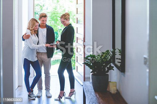 istock Real estate agent showing a young couple a new house. 1156630300