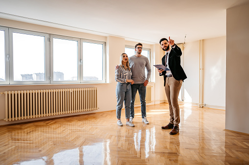 Beautiful young couple buying an apartment with a help of a real estate agent.
