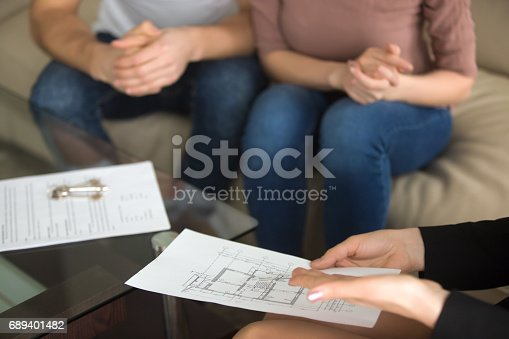istock Real estate agent showing apartment plan to couple of buyers 689401482