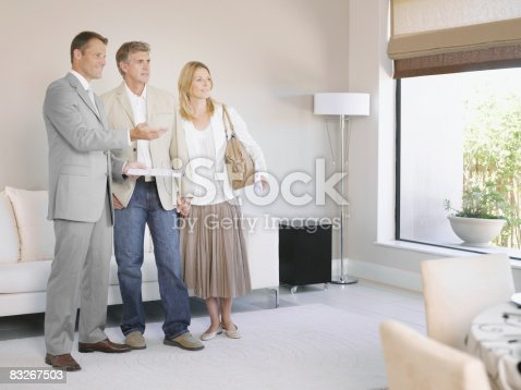 istock Real estate agent showing couple new home 83267503