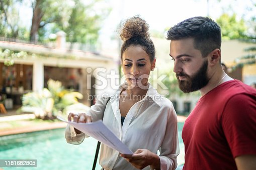 Real estate agent showing papers and talking to a clinet while visitng a house