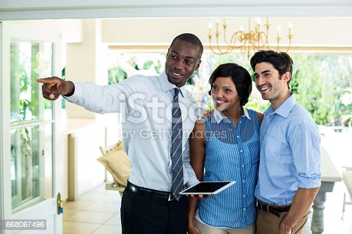 istock Real estate agent showing the house to couple 668067496