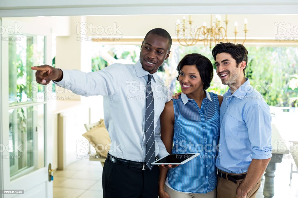 Real estate agent showing the house to couple stock photo