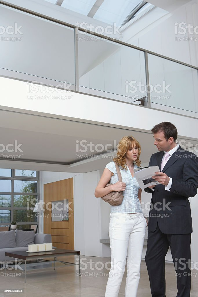 Real Estate Agent Showing Woman New House Plans royalty-free stock photo