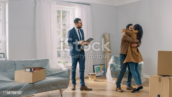 istock Real Estate Agent Shows Bright New Apartment to a Young Couple. Successful Young Couple Becoming Homeowners, Embraces and Hugs Each Other. Spacious Bright Home with Big Windows. 1158769197