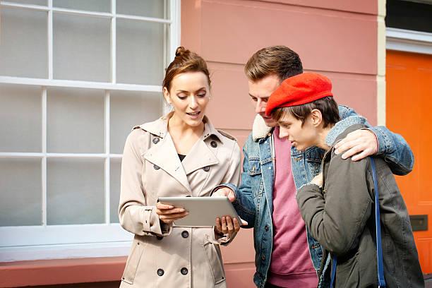 real estate agent zeigt die hotel-details zum paar mit tablet - frisch verheirateten beratung stock-fotos und bilder