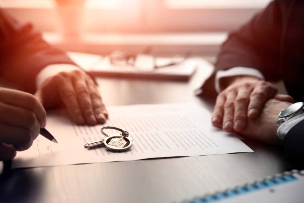 real estate agent signing a contract buy-sell home - real estate law stock photos and pictures