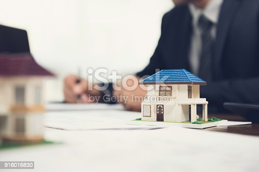 istock Real estate agent signing document with house model on the table 916016830