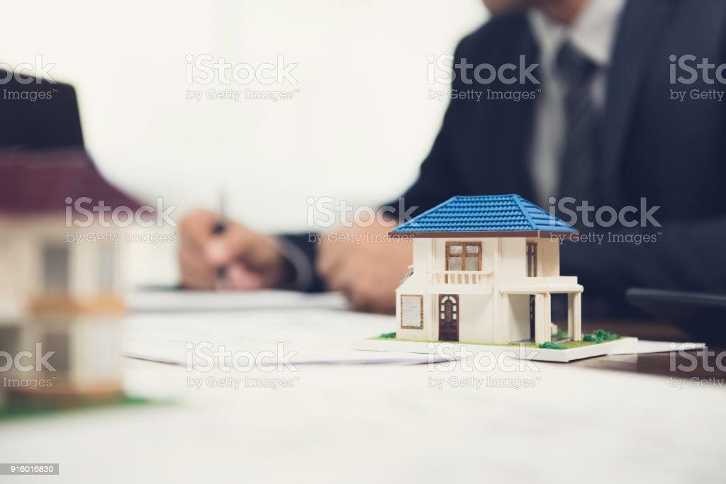Agente de bienes raíces, firma de documento con el modelo de casa en la mesa - foto de stock