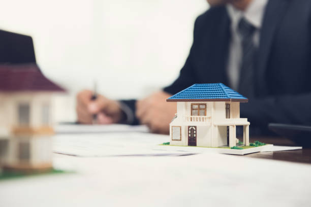 real estate agent signing document with house model on the table - imobiliaria imagens e fotografias de stock