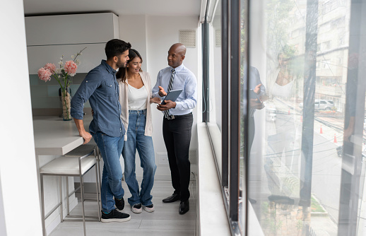 Real estate agent talking to a couple buying an apartment and showing them the blueprints of a property on his tablet computer - real estate concepts