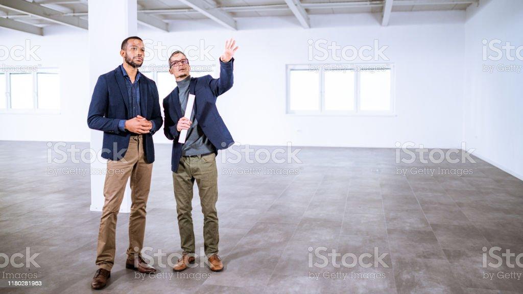 Immobilienmakler im Gespräch mit Unternehmer in einem leerstehenden Bürogebäude - Lizenzfrei Afrikanischer Abstammung Stock-Foto
