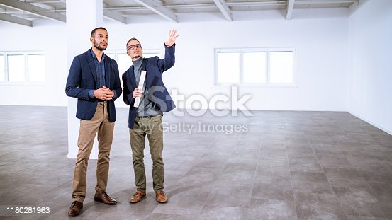 Real estate agent explaining office building properties to potential client.