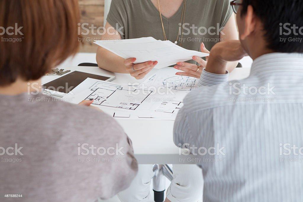Real estate agent to explain the design plan to couple stock photo