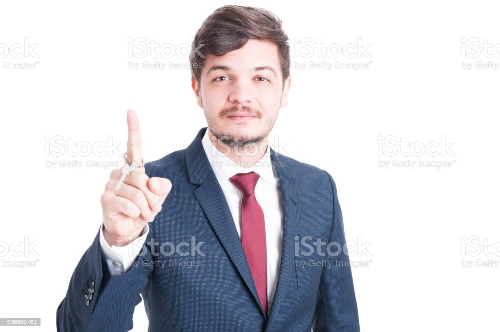 Real estate agent wearing suit holding key and rolling it stock photo