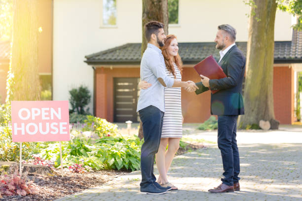 Real estate agent welcoming visitors stock photo