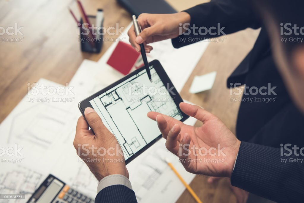 Real estate agent with client or architect team checking a housing model and its blueprints digitally using a tablet stock photo