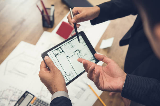 real estate agent with client or architect team checking a housing model and its blueprints digitally using a tablet - esaminare foto e immagini stock
