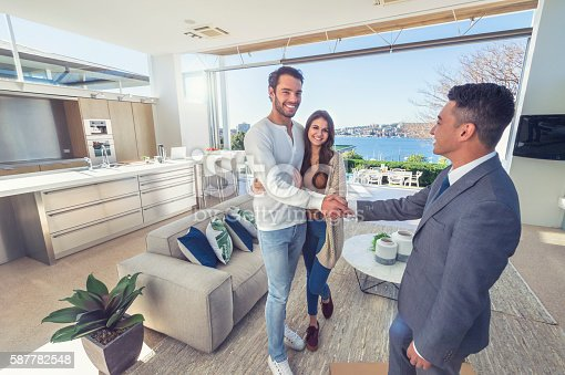 1040654052 istock photo Real estate agent with couple in luxury home. 587782548