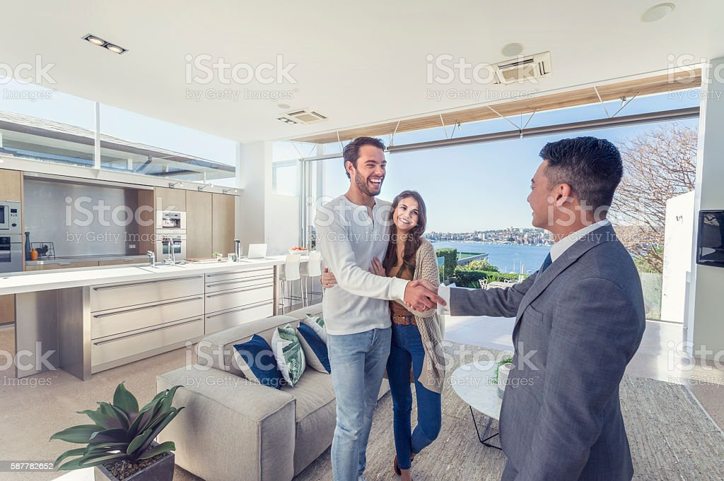 Real estate agent with couple in luxury home. royalty-free stock photo