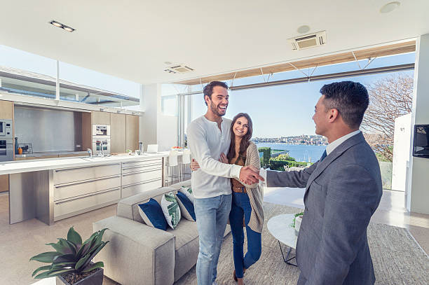 real estate agent with couple in luxury home. - selling stock pictures, royalty-free photos & images