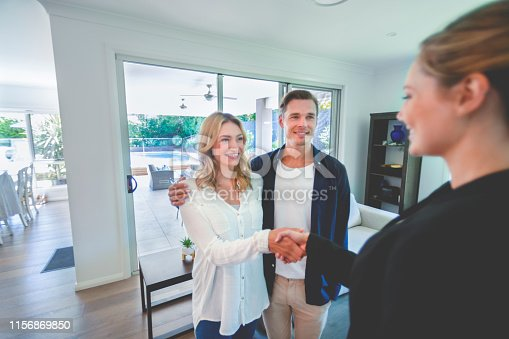 1040654052 istock photo Real estate agent with couple in luxury home. They are shaking hands 1156869850