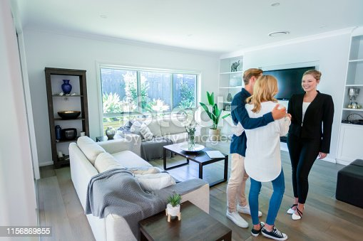 1040654052 istock photo Real estate agent with couple in luxury home. They are shaking hands. 1156869855