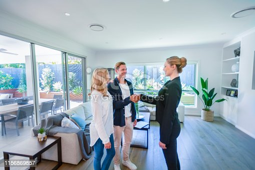 1040654052 istock photo Real estate agent with couple in luxury home. They are shaking hands. 1156869857