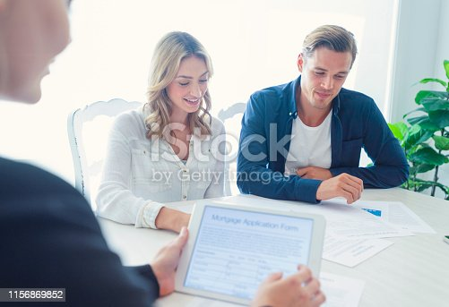 istock Real estate agent with couple looking through documents. 1156869852