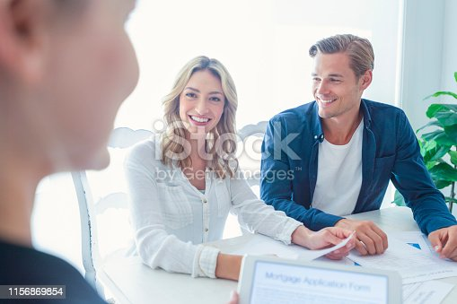 istock Real estate agent with couple looking through documents. 1156869854