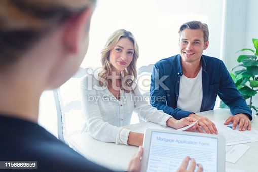 istock Real estate agent with couple looking through documents. 1156869859