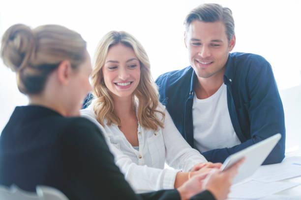 Immobilienmakler mit Paar durch die Dokumente. – Foto