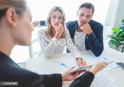 Real estate agent with couple looking through documents. The agent is holding a digital tablet showing it to the clients. Couple are casually dressed. They are looking concerned and worried and upset. Over the shoulder view.