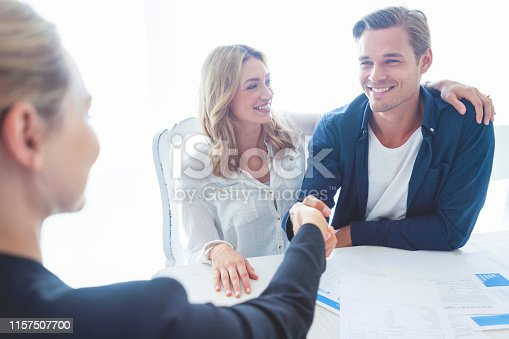 Real estate agent with couple shaking hands closing a deal. There is a digital tablet on the table. Couple are casually dressed. They are looking happy and smiling. Over the shoulder view inside a home.