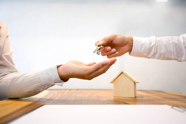Real Estate agent with customer making contract signature giving a key buy / rent a house stock photo